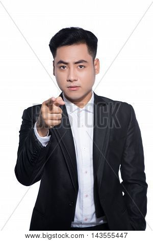 Angry young businessman standing and pointing finger at you