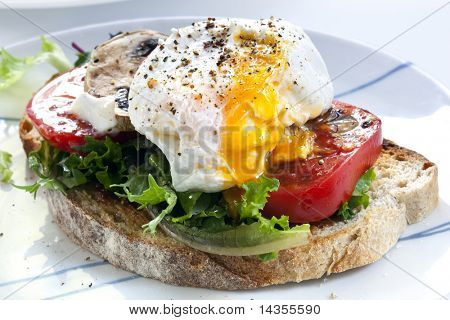Poached egg on sourdough toast, with grilled tomatoes, mushrooms and salad leaves.  A healthy, delicious breakfast or brunch.