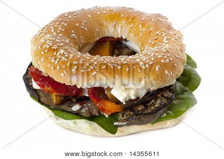 Bagel with roasted vegetables, spinach leaves, and feta cheese.