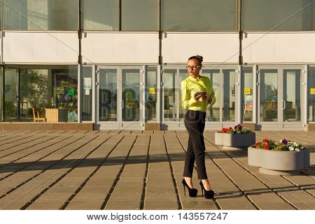 Girl waiting for a letter by e-mail outdoors. Business woman standing near office center. Correspondence. Wireless technologies.