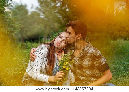 Enamoured teens together. Girlfriend and boyfriend together. The boy hugs a girl. A girl holding a bouquet of wildflowers. Creative shooting. First love. He falls in love. Date.