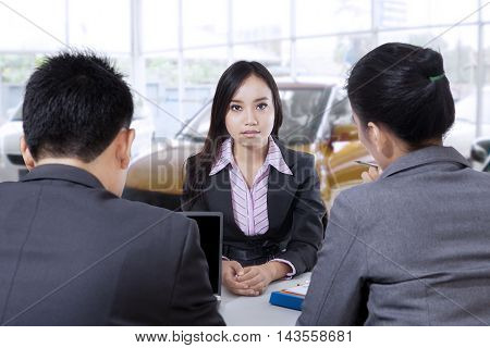 Portrait of two business people interviewing a female applicant on the car showroom