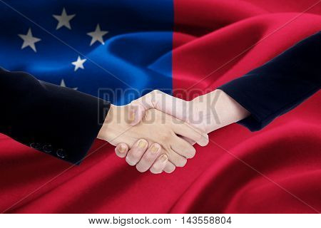 Photo of business handshake with two worker hands closing a meeting and shaking hands with Samoa flag background