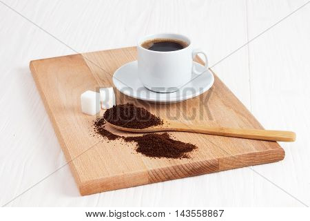 Cup of ground coffee in a wooden spoon on the table