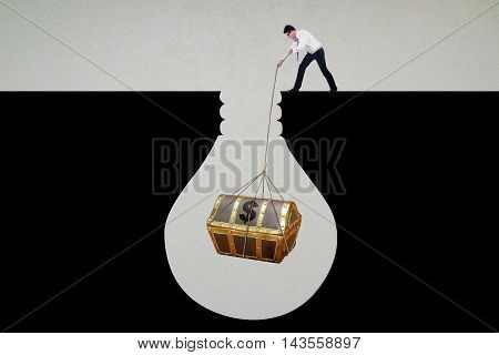 Image of a young businessman pulling a treasure chest with a rope