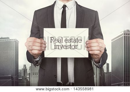 Real estate investor on paper what businessman is holding on cityscape background