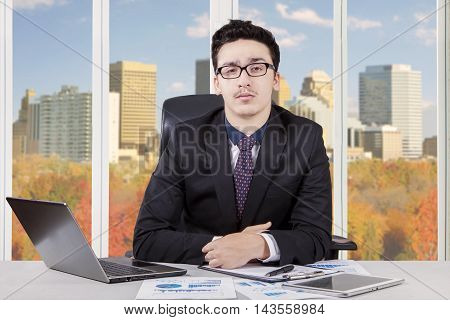 Photo of confident businessman working in the office while wearing formalwear and looking at the camera