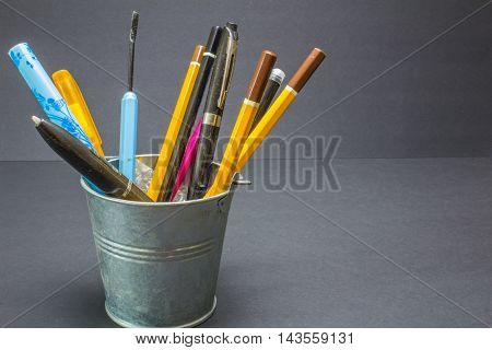 Bright Stationery Objects In Mini Pail On Black Background