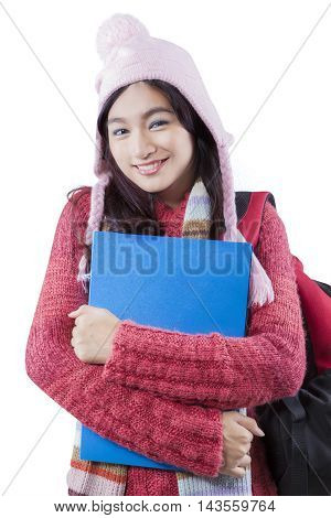 Picture of a cute female high school student smiling at the camera while wearing winter clothes in the studio isolated on white background