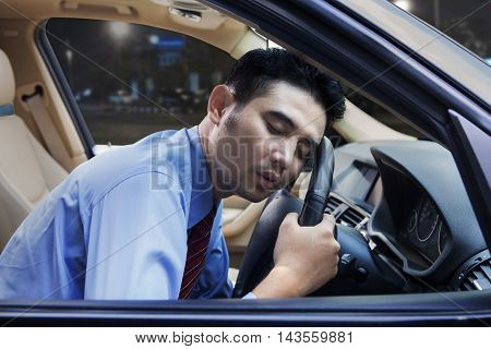 Portrait of a tired worker sleeping in the car while holding the steering wheel