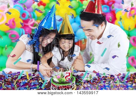 Portrait of happy family cutting a birthday cake together while smiling happy