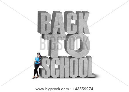 Attractive female learner standing near the text of back to school isolated on white