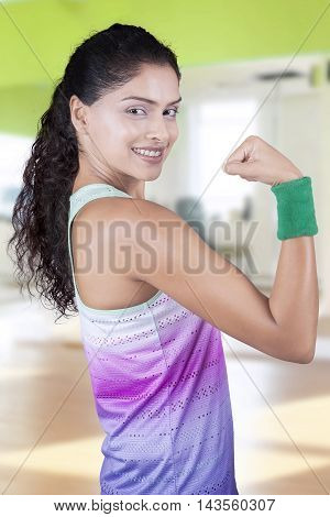 Attractive indian woman with sportswear standing at the gym and showing her bicep