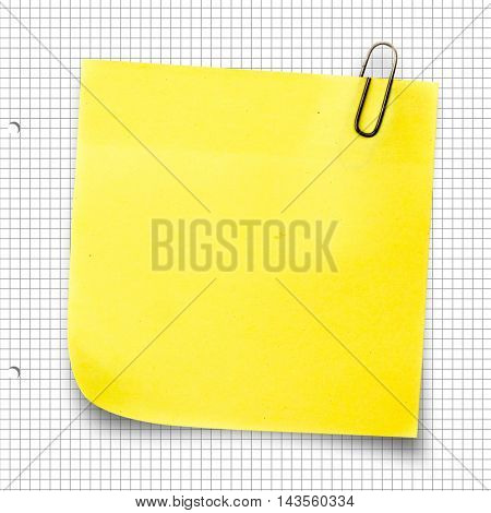 Yellow sticky note with paper clip against spiral notepad
