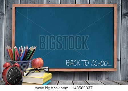 Back to school message against blackboard with copy space on wooden board