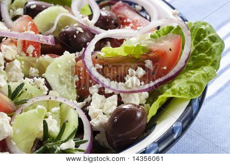 Close-up of bowl of Greek salad.  Luscious vine-ripened tomatoes, with feta cheese, kalamata olives, cucumber, red onion, kos lettuce and rosemary.