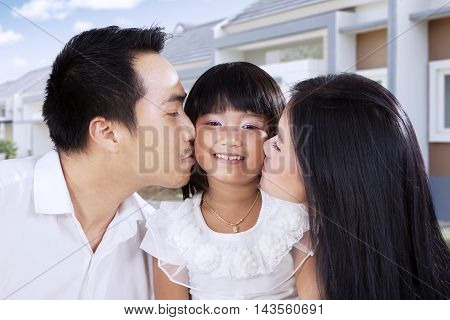Portrait of a cheerful little girl kissed by her parents in front of their new house