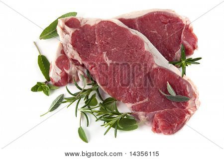 Raw sirloin steaks, with fresh herbs including rosemary, sage and oregano.  Isolated on white.