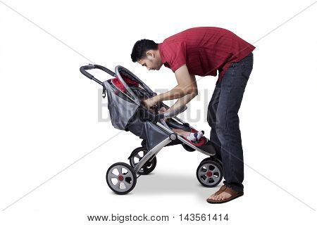 Portrait of a young man and his baby inside a stroller isolated on white background