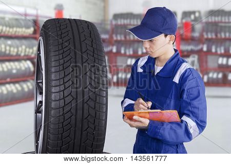 Young mechanic wearing uniform while checking tires in the workshop and write on the clipboard