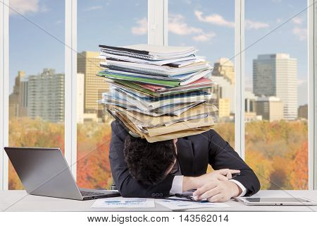 Image of tired businessman sleeping on the table with a pile of documents on his head shot in the office