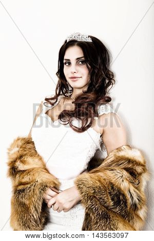 close-up portrait of young beautiful bride in a wedding dress with a wedding makeup and hairstyle. young bride in a fur coat from a red fur.