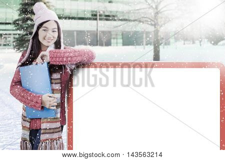 Beautiful schoolgirl standing next to empty billboard while wearing winter clothes at school yard