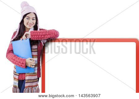 Female high school student wearing winter clothes and standing next to empty whiteboard isolated on white background
