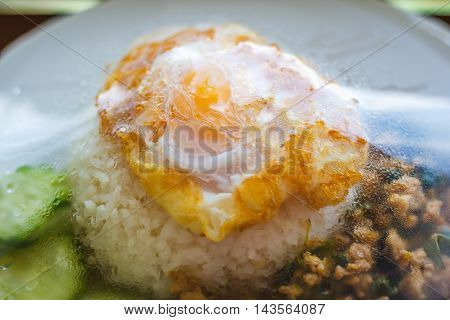 Rice topped with stir-fried chicken basil and fried egg fried stir basil with minced chicken on white background