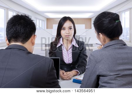 Portrait of young female applicant looking at camera during job interview in the office