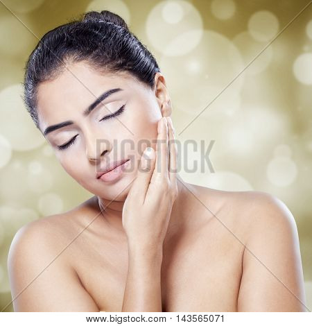 Attractive young woman with perfect skin touching her face against light glitter background