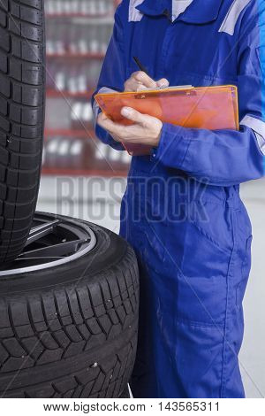 Male workshop worker checking tires while wearing blue uniform and writing on the clipboard in the garage