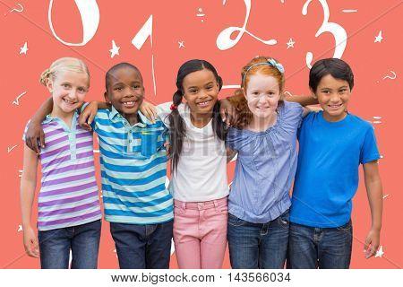 Cute pupils smiling at camera in classroom against orange