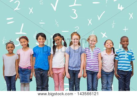 Cute pupils smiling at camera in classroom against blue background