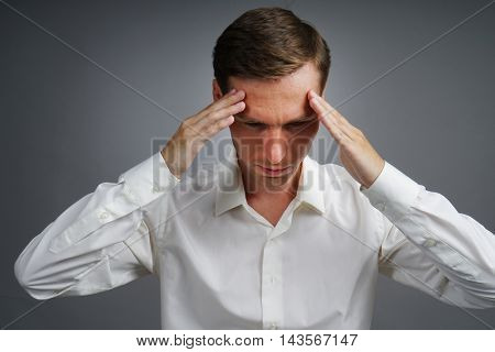 Young man in white shirt thinking or experiencing headaches.
