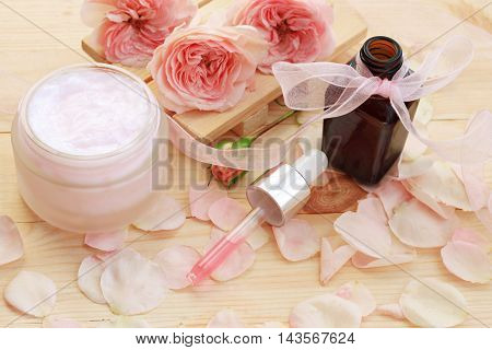 Facial rose treatment cosmetic cream container, pink essential oil dropper, fresh flowers,petals,ribbon.  Feminine toiletries on wooden bathroom spa shelf.