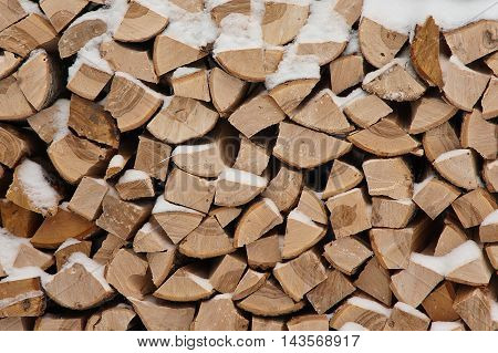 Large pile of firewood under the snow