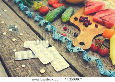 Fruits, vegetables, measure tape, pills on wooden background. Concept of different ways to lose weight. Toned image.