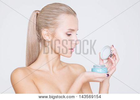 Portrait of beautiful women with perfect skin holding cream on grey background