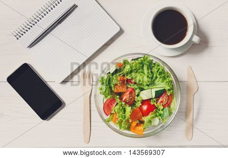 Healthy business lunch in office, top view of vegetable salad on white wooden desk with wood cutlery. Salad bowl, coffee, mobile phone and notepad with pen flat lay. Snack at break time