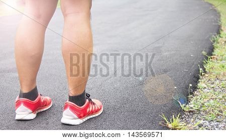 Running Sport Shoes On Runner. Legs and Running Shoe Closeup Of Man Jogging Outdoors On Public Park