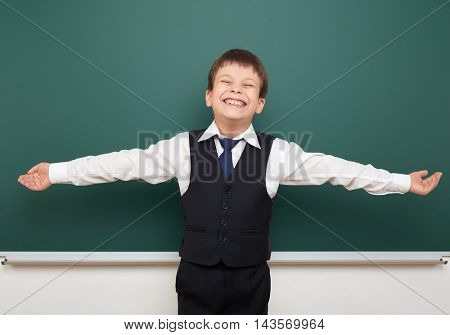 school student boy posing at the clean blackboard and open arms, grimacing and emotions, dressed in a black suit, education concept, studio photo