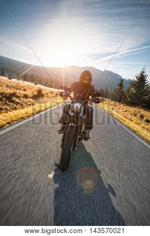 Motorcycle driver riding on motorway in beautiful sunset light. Shot from front view