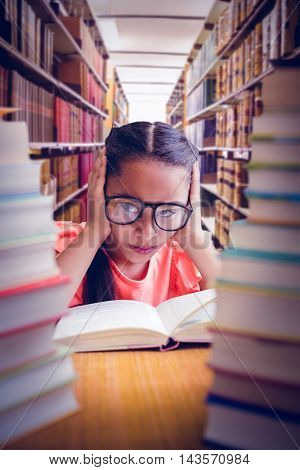 Frustrated girl seen through book stack against close up of a bookshelf