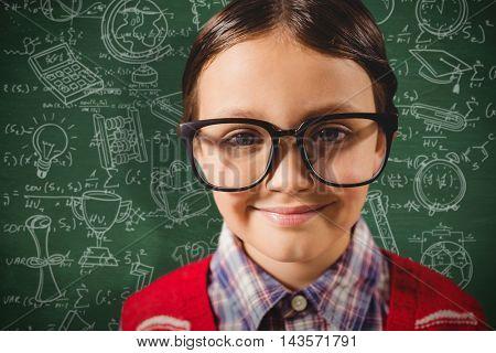 Little boy wearing glasses against green chalkboard