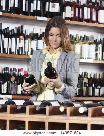 Mid Adult Woman Choosing Wine Bottles
