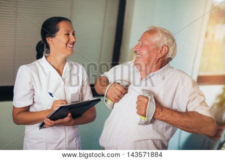 Senior man with dumbbells in rehab with a physiotherapist
