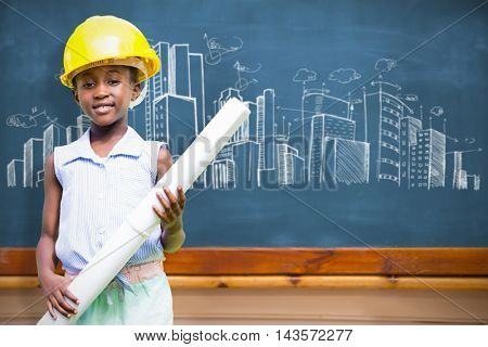 Little girl wearing yellow helmet and construction plan against blackboard