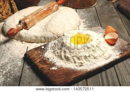 Egg yolk in flour on wooden board in the bakery. Bakery backgrounds