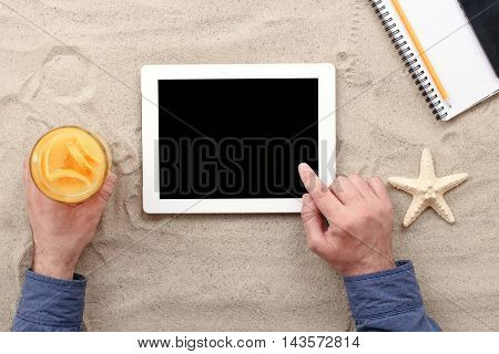 Man working on the beach remotely using tablet. Top view